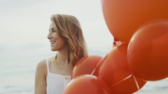 vídeos de stock e filmes b-roll de beautiful woman holding red balloons on the beach - mulher balões