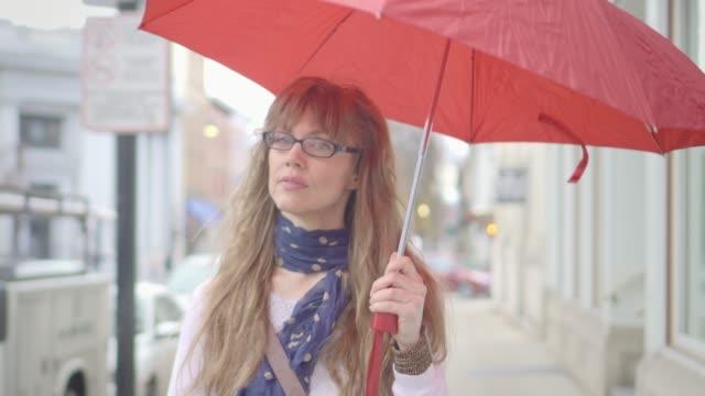vidéos et rushes de belle femme avec parapluie rouge se promène sous la pluie - 40 44 ans