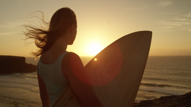 SLOW MOTION CLOSE UP: Beautiful woman holding surfboard gazing at the sunset. video