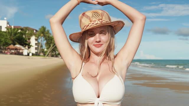 A beautiful woman in a bikini is walking on the beach, taking a summer break.