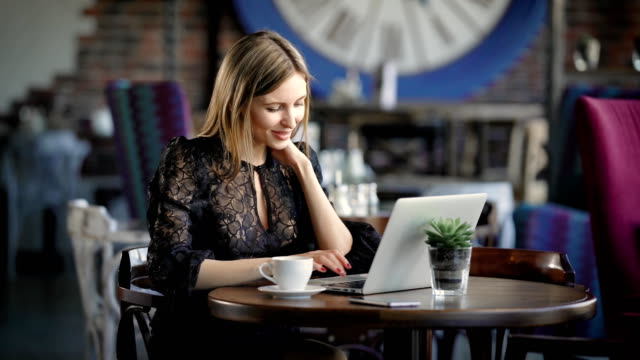 vidéos et rushes de belle femme dans un café avec un ordinateur portable. une fille joyeuse, heureuse, impressions sur le clavier de l'ordinateur portable, elle a reçu de bonnes nouvelles et leur partage via les médias sociaux - travailleur indépendant