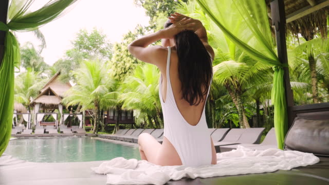 vídeos de stock e filmes b-roll de a beautiful woman in a luxury resort, relaxes on loungers by the pool and while swimming. - mulher natureza flores e piscina