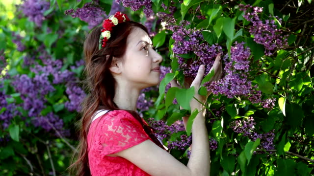 beautiful woman in a red dress walks in the park among the lilac
