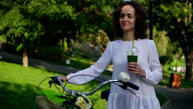 Beautiful woman in a white shirt and blue jeans walking in the city park holding her city bicycle's handlebar with flowers in its basket and drinking green detox smoothie. Healthy lifestyle video