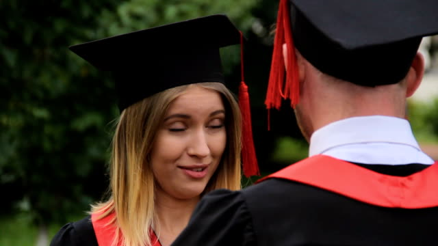 beautiful woman in academic dress talking to graduating boyfriend after ceremony - compagni scuola video stock e b–roll