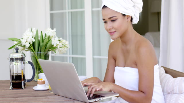 Beautiful woman in bath towel using laptop Beautiful woman wrapped in white towel working at table on her laptop computer beside flowers and coffee outside wearing a towel stock videos & royalty-free footage