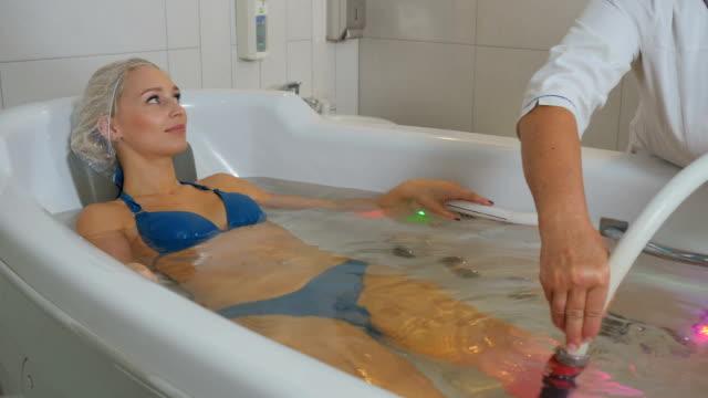 beautiful woman in bikini enjoys the hydromassage procedures in bathtub - china drug video stock e b–roll