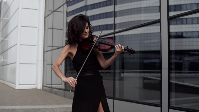 Beautiful woman in black dress playing violin near glass building. Art concept Beautiful woman in black dress playing violin near glass building. Urban art concept. Medium shot musical theater stock videos & royalty-free footage