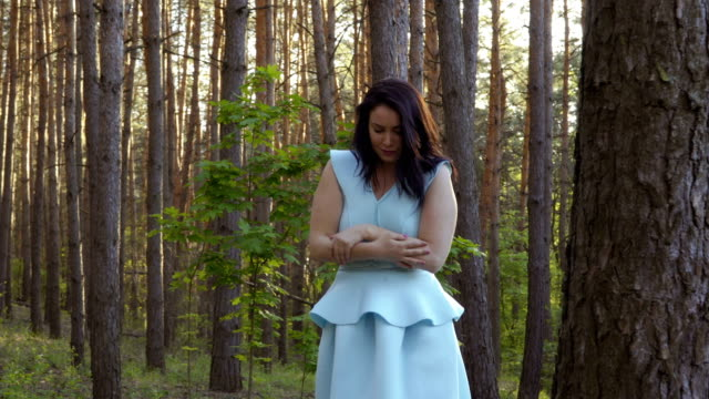 beautiful woman in blue dress wave off from insects in the forest - pasożyt filmów i materiałów b-roll