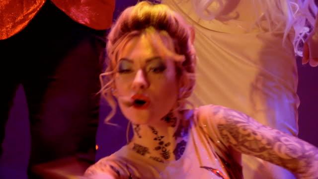 stockvideo's en b-roll-footage met mooie vrouw in lichte kostuum zingt lied microfoon op het podium - vetschmink