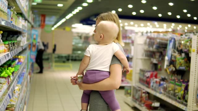 Beautiful woman in glasses holding her child in her arms while choosing baby food on the shelves in the supermarket. fruit puree and juices for children, carefully choosing products for her child video