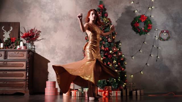 vacker kvinna i gyllene aftonklänning snurrar och dansar nära julgran - aftonklänning bildbanksvideor och videomaterial från bakom kulisserna
