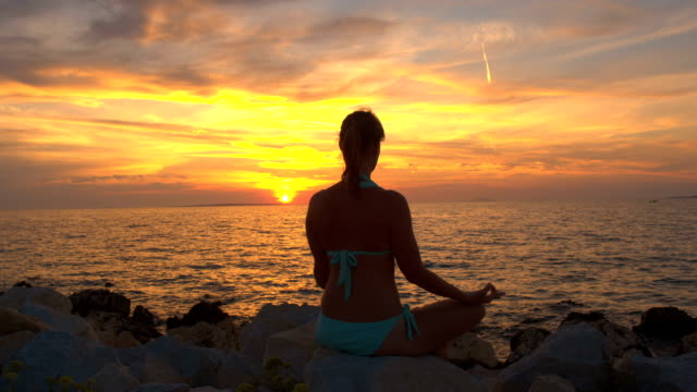 CLOSE UP: Beautiful woman in lotus yoga position by the ocean on magical evening