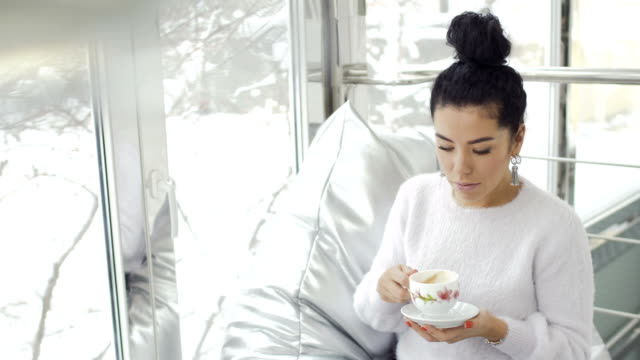 Beautiful woman in white sweater sits near window and drinks coffee video