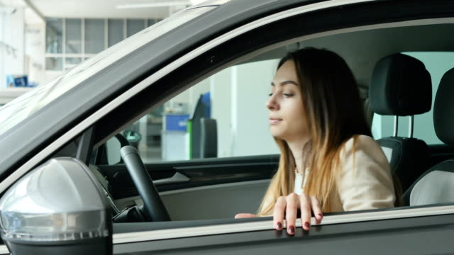 Beautiful woman inspects the cabin of modern car in showroom video