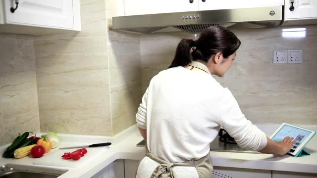 vídeos de stock e filmes b-roll de beautiful woman interacting with digital tablet in kitchen - avental
