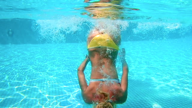 Beautiful woman is diving underwater in water pool video
