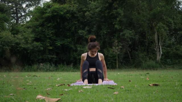 beautiful woman is doing yoga in park - gambe incrociate video stock e b–roll