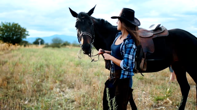 Beautiful woman is enjoying nature with her horse Beautiful young woman is walking with her horse outdoors in nature , on a sunny day cowgirl stock videos & royalty-free footage
