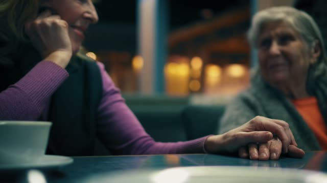 beautiful woman is holding and caressing her mother's hand in cafe. mother and grandmother are lovely smiling to each other. - rispetto video stock e b–roll