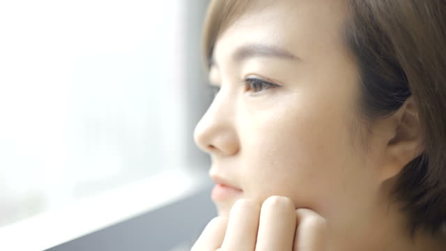beautiful woman is thinking by the window