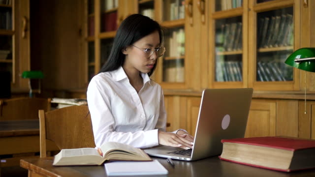 Beautiful woman is using laptop, reading book sitting at table in library