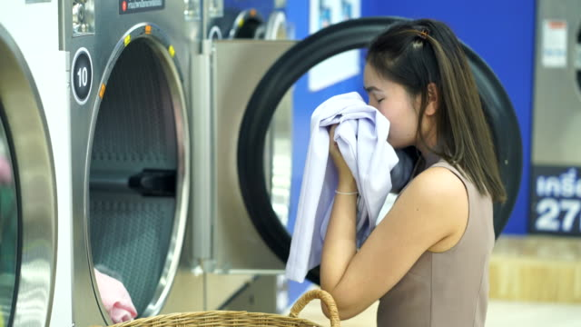 beautiful woman is washing clothes in an automatic laundry shop.