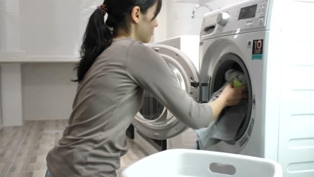 güzel kadın otomatik bir çamaşırhanede giysi yıkama - ev temizleme stok videoları ve detay görüntü çekimi