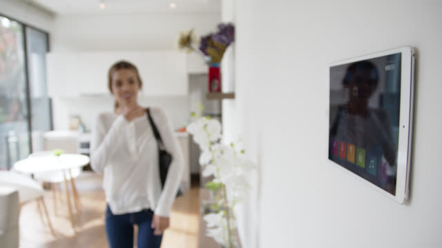 Beautiful woman leaving locking her smart home through tablet Beautiful woman leaving locking her smart home through tablet - technology concepts home interior stock videos & royalty-free footage