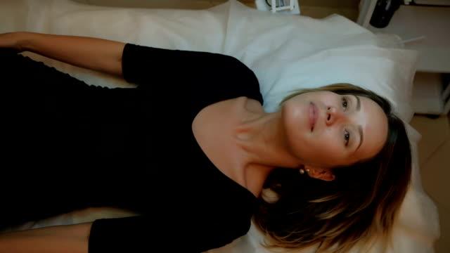 Schöne Frau auf der Couch liegen und mach dich bereit für kosmetische Eingriffe – Video