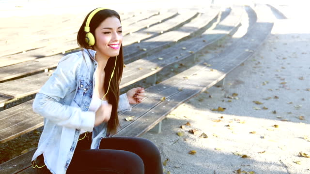 Beautiful woman listening to music on headphones and dancing to the rhythm video