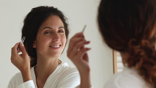 vídeos de stock e filmes b-roll de beautiful woman looking in mirror holding tweezers plucks eyebrows - puxar cabelos