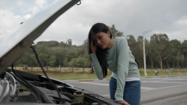 Beautiful woman looking under the hood of the car very upset needing roadside assistance