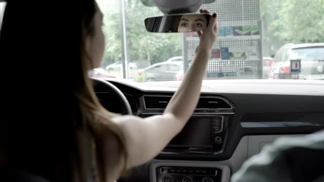 아름 다운 여 자가 자동차의 오두막에 리어 뷰 미러에서 보이는 - 검사 보기 스톡 비디오 및 b-롤 화면