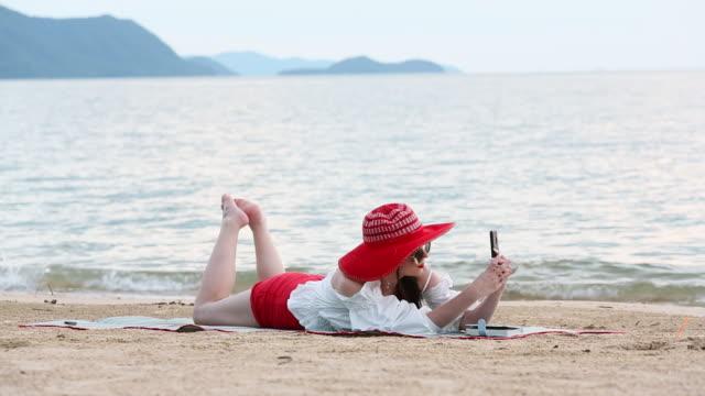 Bella mujer acostada en la arena con felicidad en el chat relajante y en línea de playa al atardecer - vídeo