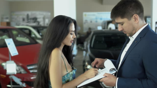Beautiful woman makes a successful deal of buying car in car dealership Beautiful woman makes a successful deal of buying car in car dealership. The customer signs the agreement in salesman's hands. The manager gives a car keys to happy purchaser and people looks in camera and smiling. car rental stock videos & royalty-free footage