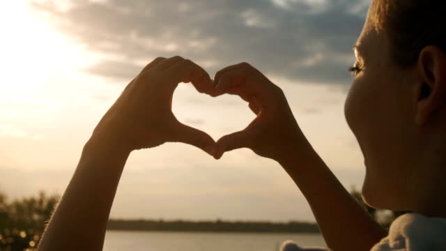 Beautiful Woman making heart shape with hands at sunset Beautiful Woman making heart shape with hands at sunset Girl holding up love symbol gesture with orange sun flare low lighting stock videos & royalty-free footage