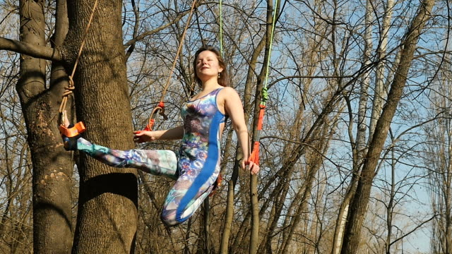 Beautiful woman meditates on the ropes in park Young woman practicing aerogravity in the park. The woman makes physical exercises on the ropes on tree. Flexible female hanging on the ropes and stretching her body and muscles. She's moving slowly and accuracy. arthropod stock videos & royalty-free footage