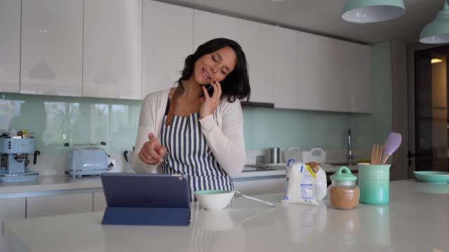 vídeos y material grabado en eventos de stock de hermosa mujer multi tarea en casa preparando la comida, en una llamada telefónica y mirando la tableta - woman cooking