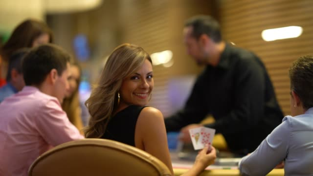 Beautiful woman on a lucky strike at the casino playing blackjack looking at camera smiling