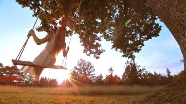 SLO MO Beautiful woman on a swing in sunset video