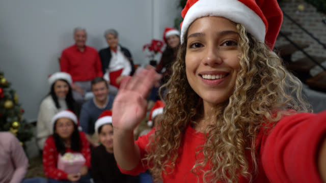beautiful woman on a video conference and everyone at background waving while she talks during a christmas celebration at home - video call with family video stock e b–roll