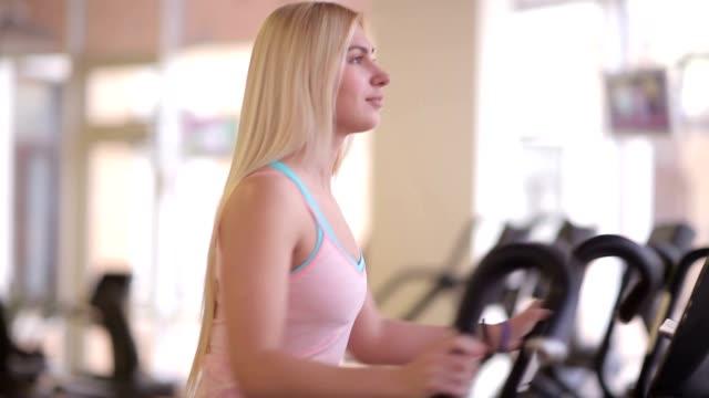 Beautiful woman on orbitrek elliptical trainer video