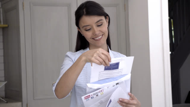 Beautiful woman opening her mail and receiving good news