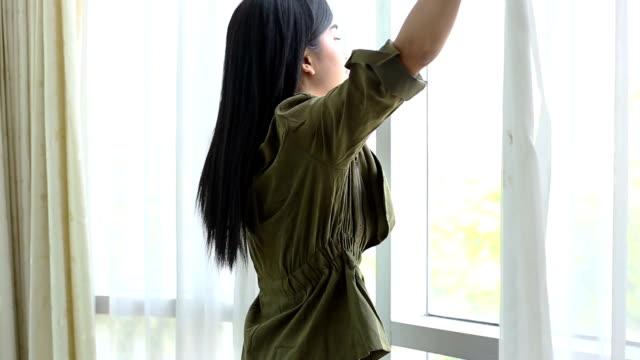 美しい女性は、家のカーテンを開きます。 ビデオ