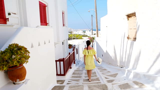 Beautiful woman outdoors in old streets an Mykonos. Girl at street of typical greek traditional village with white walls and colorful doors on Mykonos Island, in Greece, Europe video