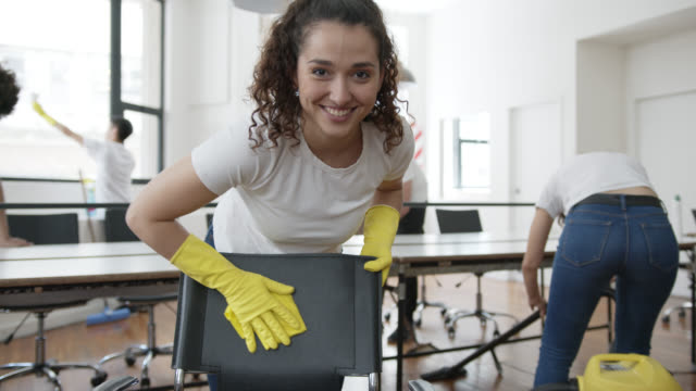 beautiful woman part of a team cleaning team at an office cleaning a chair and then smiling at camera - addetto alle pulizie video stock e b–roll