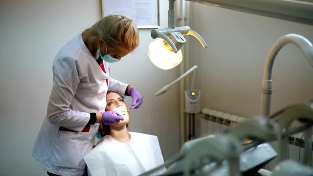 美人患者は歯科医のオフィスで歯科治療を有するします。女性彼女の歯科医を訪問 - 歯科医師点の映像素材/bロール