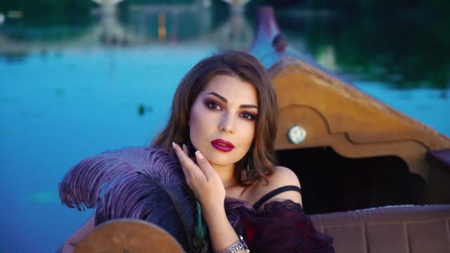 A beautiful woman playfully is glancing from under the guise of a purple feather on the gondola on a warm evening. A beautiful woman playfully is glancing from under the guise of a purple feather on the gondola on a warm evening. Blurred background. Close-up princess stock videos & royalty-free footage