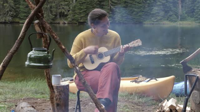 vídeos de stock, filmes e b-roll de mulher bonita brincando em ukulele na natureza, acampando na natureza, curtindo ao lado da fogueira ao ar livre. - boho
